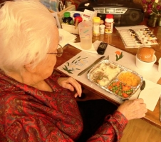 A client of Community Care's hot meals program preparing to enjoy the meal. Gift certificates are available.